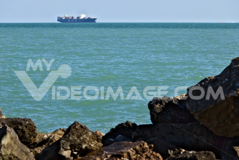 A cargo ship on the horizon in the green sea. Foto navi. Ships photo.