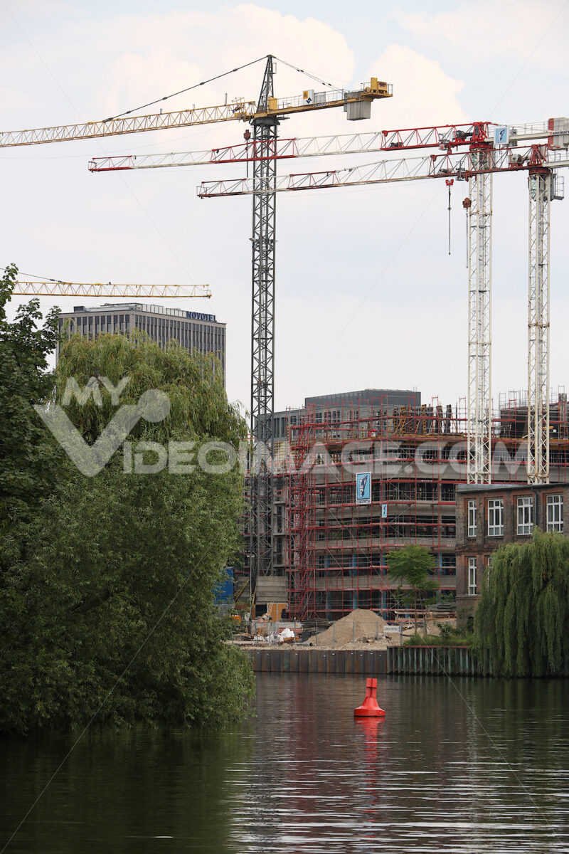A construction site on the river bank in Berlin. Tower cranes rise into the sky.  Cantieri edili. - LEphotoart.com