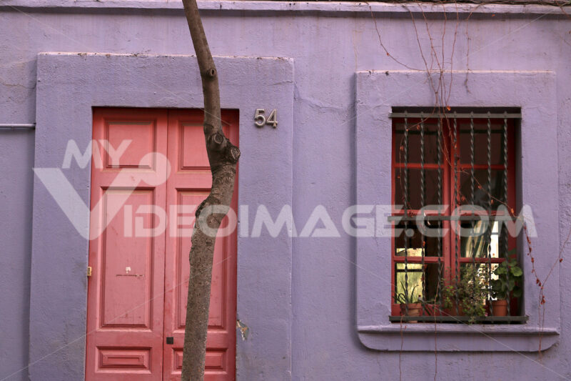 A facade of a house in Barcelona with violet colored walls. - MyVideoimage.com