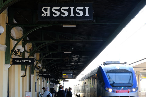 A regional train is entering the Assisi station. Billboard and shelter. Città Italiane. Foto treno. Train photo.