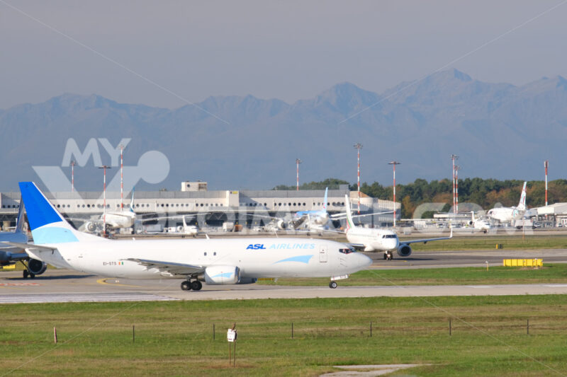 ASL Aviation Boeing 737-48E airplane on the Malpensa airport runway. In the background the buildings of Terminal 1 and parked airplanes. - MyVideoimage.com