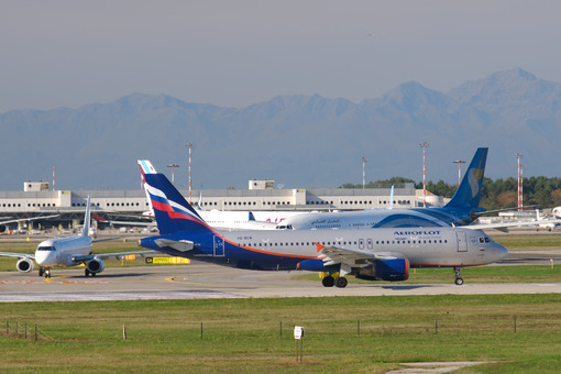 Aeroflot Airbus A320-214 airplane maneuvering on the Malpensa airport runway. In the background the buildings of Terminal 1 and parked airplanes. - MyVideoimage.com
