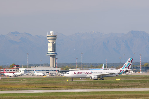Air Italy Airbus Airbus A330-202 airplane on the Malpensa airport runway. In the background the buildings of Terminal 1 and parked airplanes. - MyVideoimage.com
