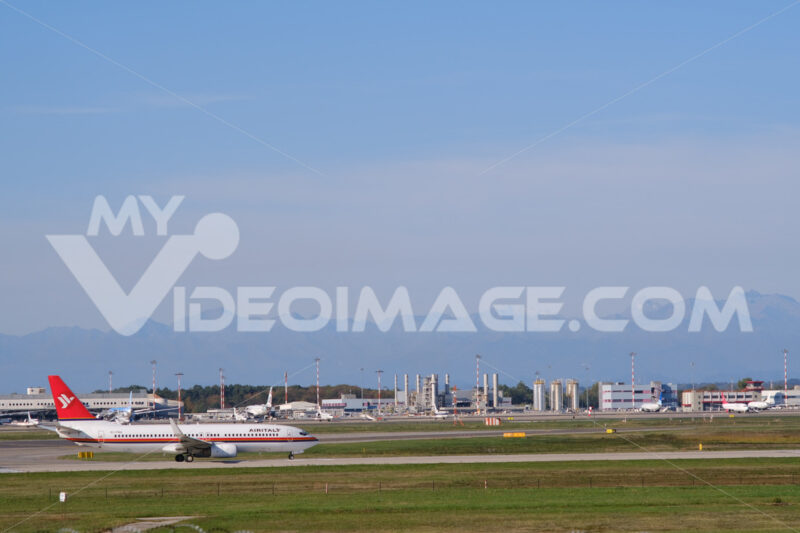 Air Italy Boeing 737-800  airplane on the Malpensa airport runway. In the background the power and thermal plant with chimneys. - MyVideoimage.com