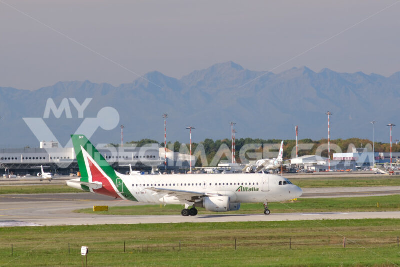 Alitalia Airbus A319-112  airplane taxiing on the Malpensa airport runway. In the background the buildings of  Cargo Terminal and parked airplanes. - MyVideoimage.com