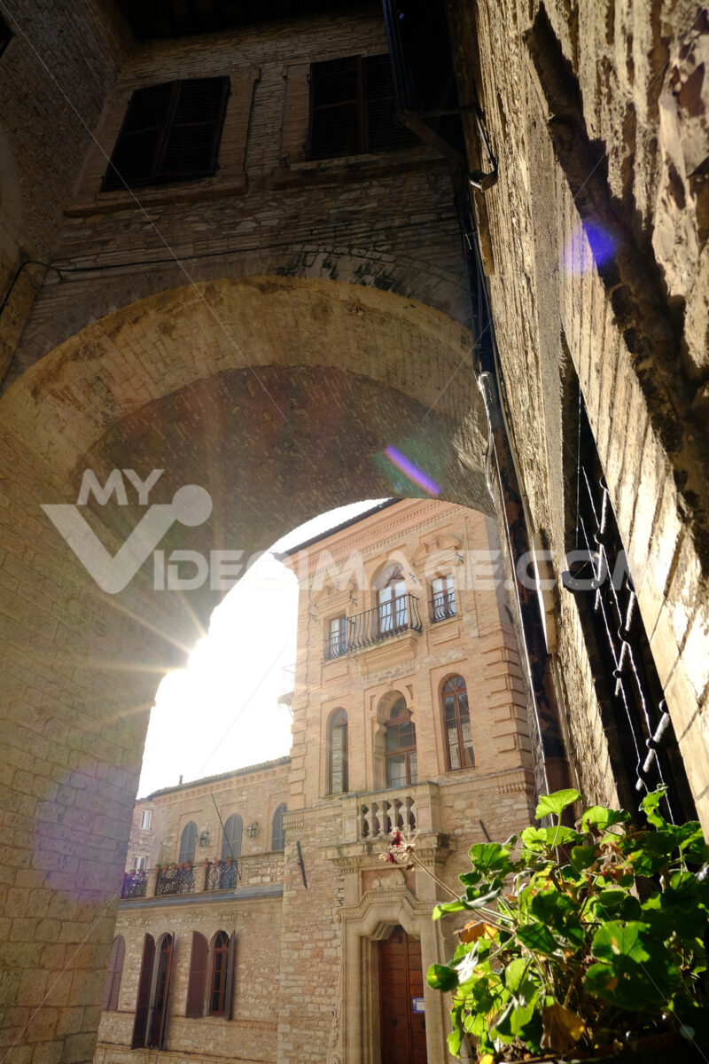 Alley of the city of Assisi with arch and vault. The walls of the houses are built with light colored stone. - LEphotoart.com