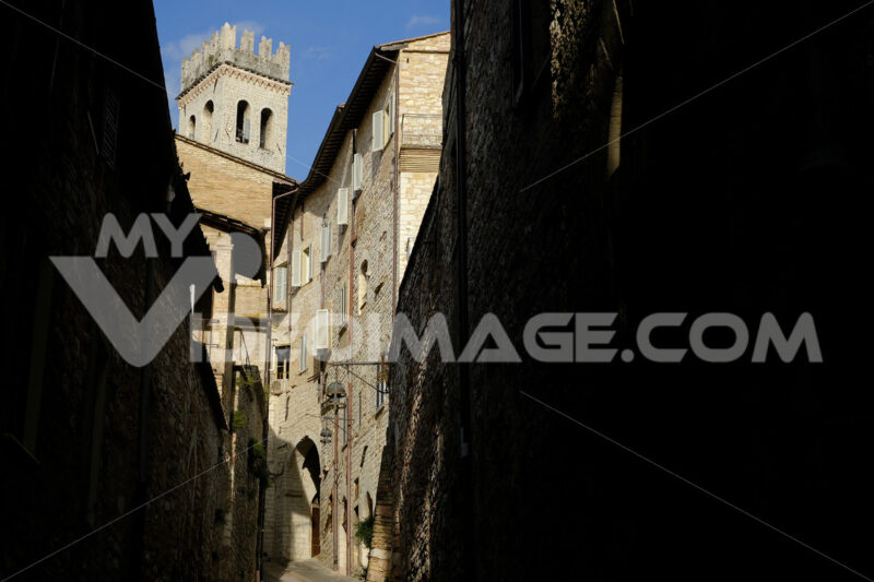 Alley of the city of Assisi with bell tower and stone houses. Narrow street of the city with the walls of the stone houses. Deserted road. - MyVideoimage.com