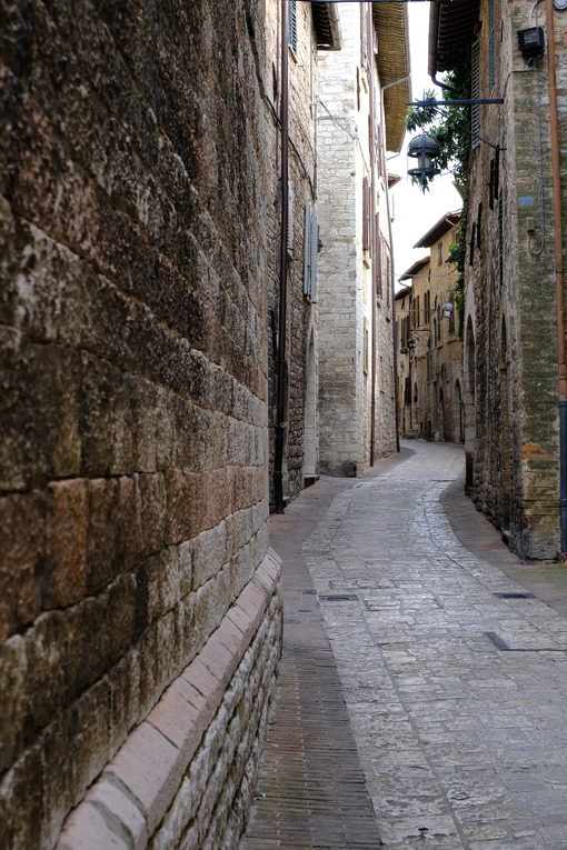 Alley of the city of Assisi with stone facades of historic houses. 	Narrow alleys of the city with the walls of the stone houses. Deserted road. - MyVideoimage.com