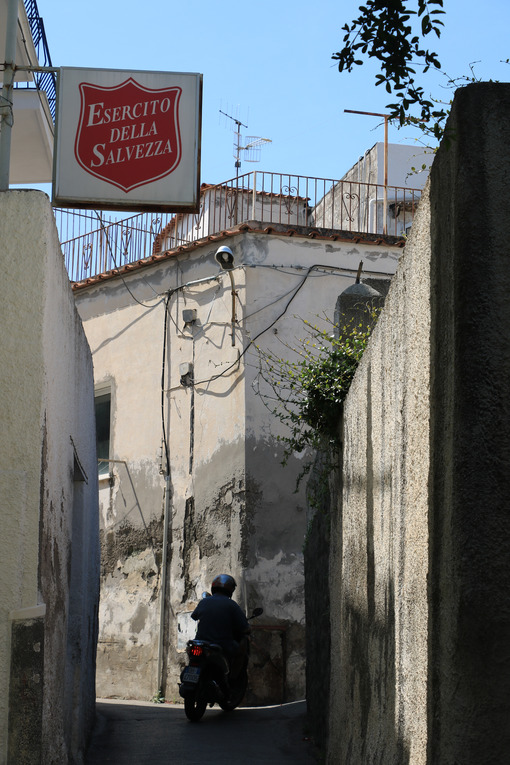 Alley with Mediterranean houses and high walls, sign of the Salvation Army. Person on a motorcycle. - MyVideoimage.com