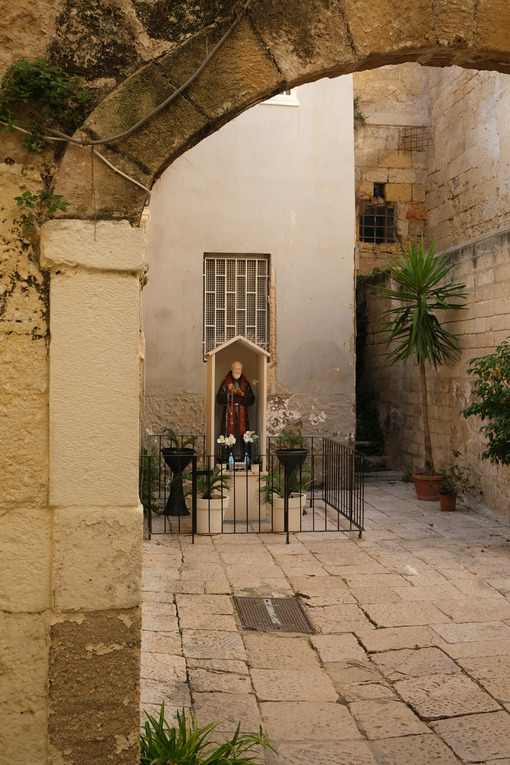 Altar with a statue of a saint in a courtyard in the historic center of Bari. Stone arch. Foto Bari photo.