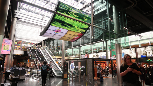 Amsterdam Airport Schiphol. Escalators. Airport terminal, shopping arcade with shops and people in transit. - MyVideoimage.com
