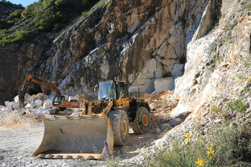An excavator and a bulldozer in a Carrara marble quarry. A large - MyVideoimage.com