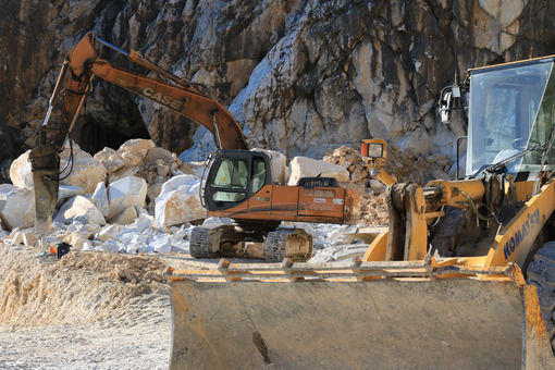 An excavator and a bulldozer in a Carrara marble quarry. A large excavator and a bulldozer in a marble quarry in the Apuan Alps. - MyVideoimage.com