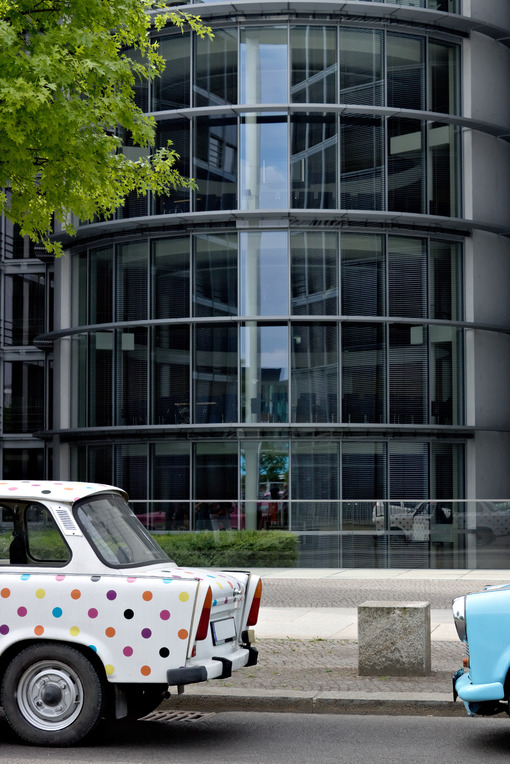 Ancient Trabant car. Vintage Trabant high-buildings parked. Foto automobili. Cars photos.