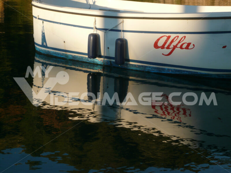 Ancient boat with the word Alfa moored at the port and illuminated by the light of the sunset. - MyVideoimage.com