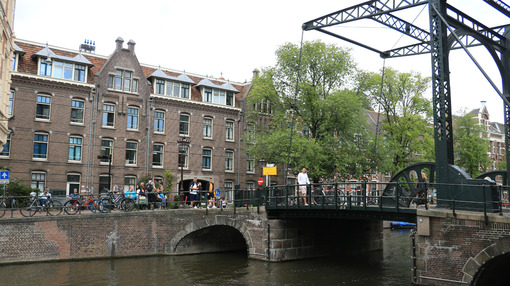 Ancient bridge on an Amsterdam canal. A boat runs along the cana - MyVideoimage.com
