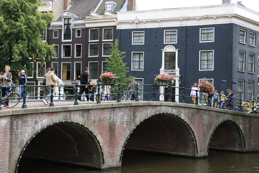 Ancient bridge on an Amsterdam canal. A boat runs along the canal. Amsterdam foto. Amsterdam photo