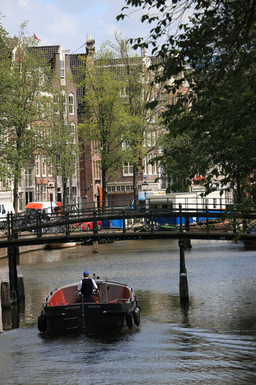 Ancient bridge on an Amsterdam canal. A boat runs along the cana - MyVideoimage.com