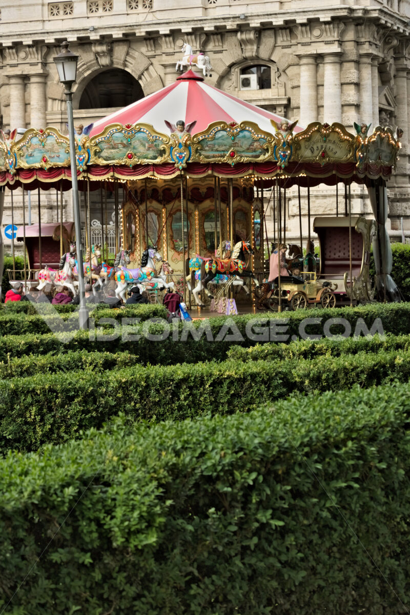 Ancient carousel in a public park. In the foreground hedges with boxwood plants. - MyVideoimage.com