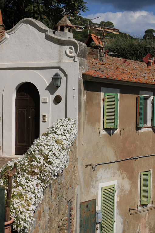 Ancient house in the village of Castiglione della Pescaia, Faciata painted in white. Wall with flowering plants. Windows with shutters. - MyVideoimage.com