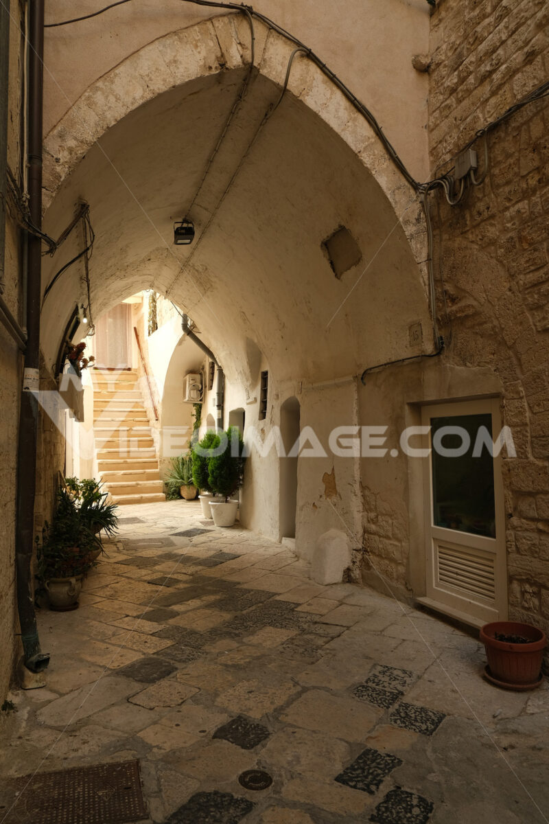 Ancient houses in the alleys of the city of Bari. Ogival vault in an alley. Marble flooring. - MyVideoimage.com