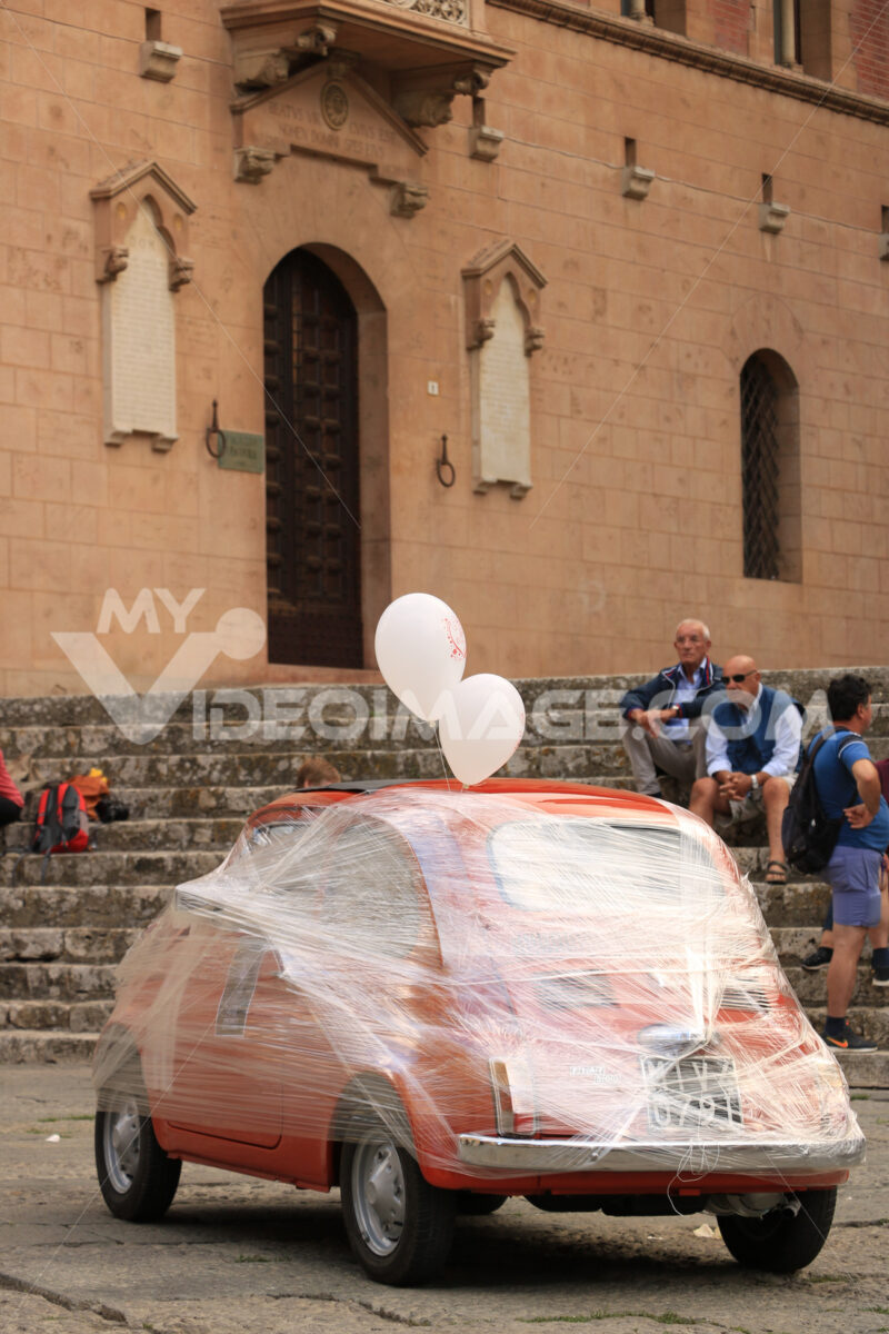 Antique red Fiat 500 car parked in the square of Massa Marittima. The car awaits the bride and groom at the cathedral wedding. Foto automobili. Cars photos.