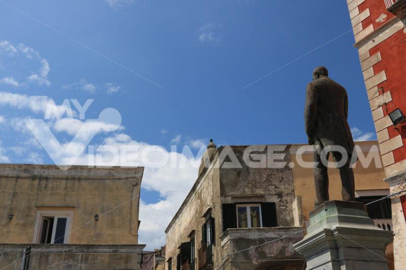 Antonio Scialoja. Bronze monument to Antonio Scialoja in a square in Procida. In the background the façades of the Mediterranean houses. - MyVideoimage.com | Foto stock & Video footage