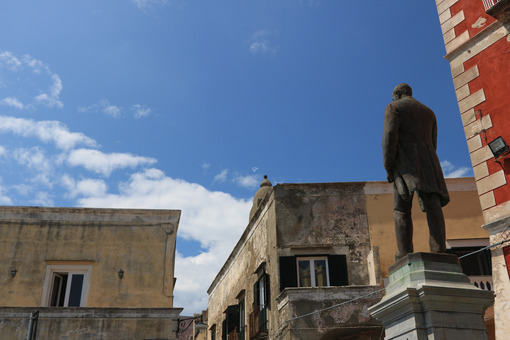 Antonio Scialoja. Bronze monument to Antonio Scialoja in a square in Procida. In the background the façades of the Mediterranean houses. - MyVideoimage.com | Foto stock & Video footage