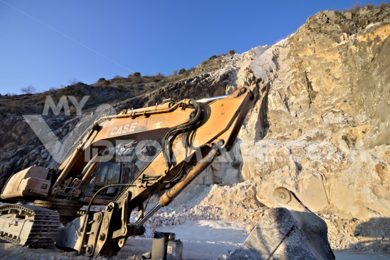 Apuan Alps, Carrara, Tuscany, Italy. March 28, 2019.  An excavator in a quarry of white Carrara marble. - MyVideoimage.com