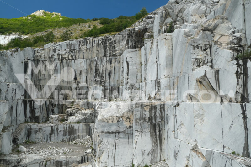 Apuan marble quarry. Wall of a white marble quarry under the mountain. Stock photos. - MyVideoimage.com   Foto stock & Video footage
