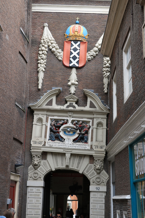 Arched door in ancient red brick building. Coat of arms of the c - MyVideoimage.com