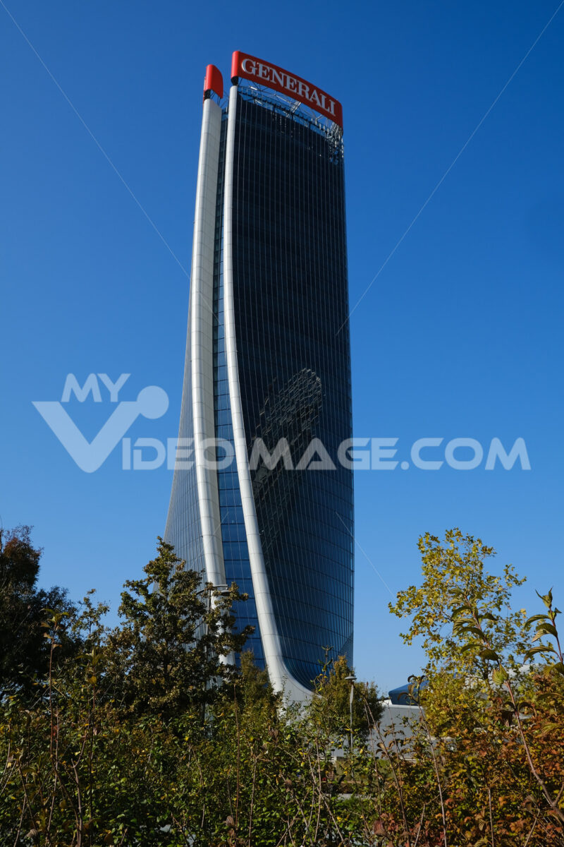 Assicurazioni Generali skyscraper with the blue sky background and trees with green leaves. Società. Company building. - MyVideoimage.com | Foto stock & Video footage
