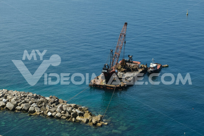 Barge with crane for dredging the seabed at the port of Riomaggiore, Cinque Terre, royalty free - MyVideimage.com