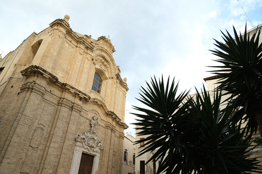 Baroque church in the city of Bari. A small church with a facade made of beige stone. Foto Bari photo.