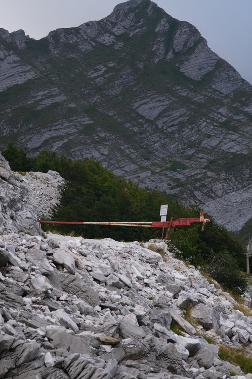 Barred road. Dirt road closed with a bar in a marble quarry on the Apuan Alps in Tuscany. Stock photos. - MyVideoimage.com | Foto stock & Video footage