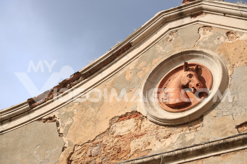 Bas-relief in terracotta with a horse's head applied to the wall - MyVideoimage.com