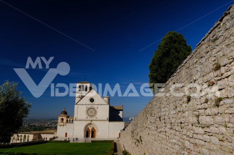 Basilica of San Francesco with the lawn with green grass in front and the blue sky. - MyVideoimage.com