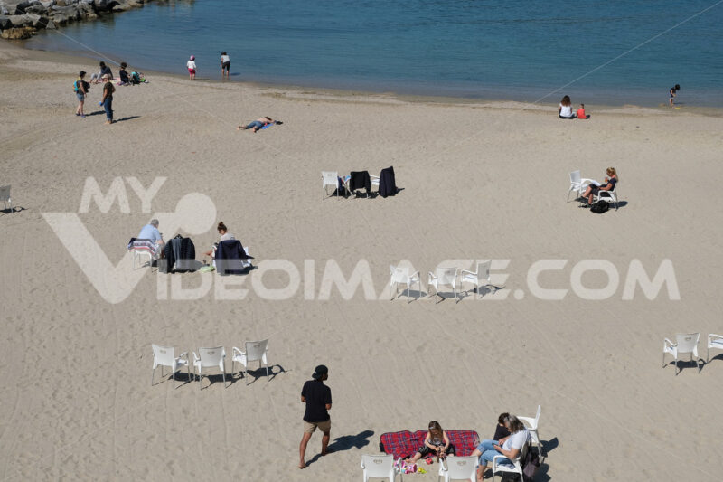 Beach with Covid. People on the beach by the sea in Liguria during the Covid-19 pandemic. Stock photos. - MyVideoimage.com | Foto stock & Video footage