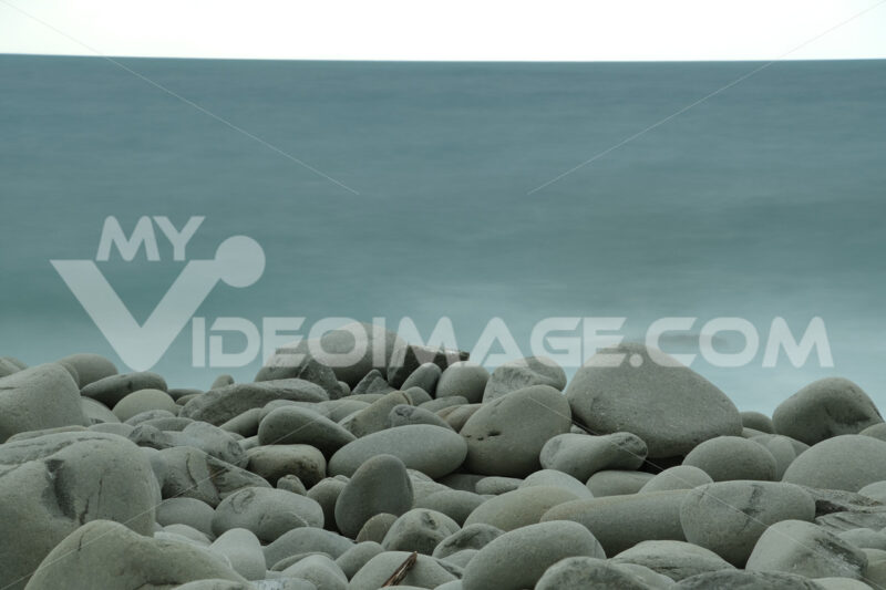 Beach with large stones near the Cinque Terre. Velvety sea with long exposure. Campiglia, La Spezia. - MyVideoimage.com