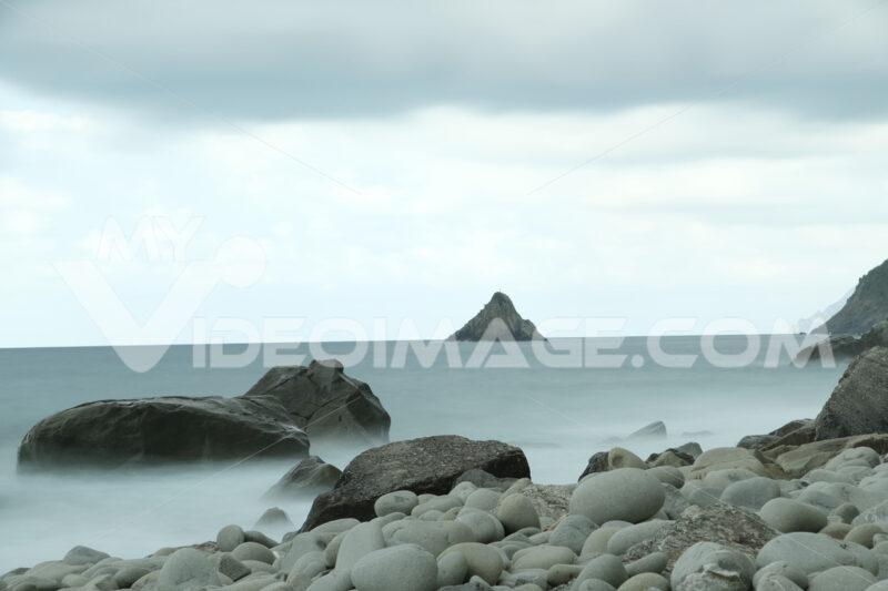 Beach with large stones near the Cinque Terre. Velvety sea with long exposure. Scoglio del Ferale, La Spezia. - MyVideoimage.com