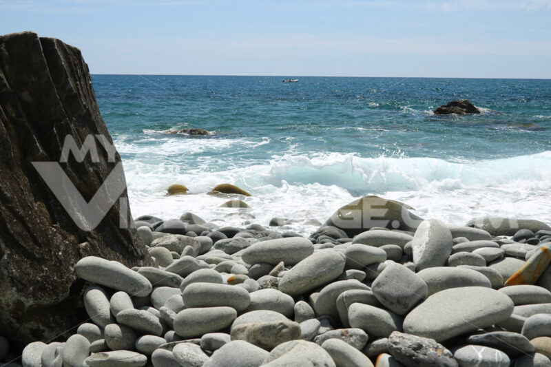 Beach with large stones near the Cinque Terre. Velvety sea with long exposure. Scoglio del Ferale, La Spezia. - MyVideoimage.com