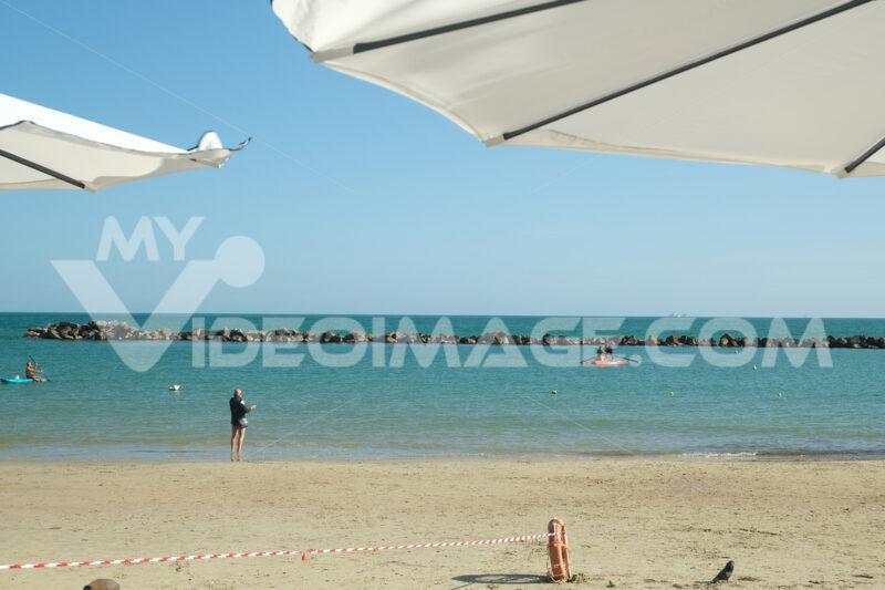 Beach with umbrella. Panorama of the sea and the beach through a white umbrella. Stock photos. - MyVideoimage.com | Foto stock & Video footage