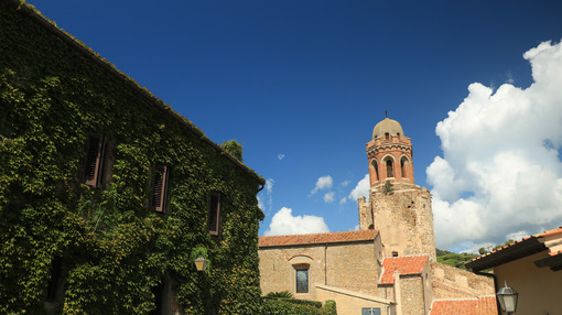 Bell tower of the church of Castiglione della Pescaia with blue sky. House with a façade covered with a creeping plant with green leaves. - MyVideoimage.com