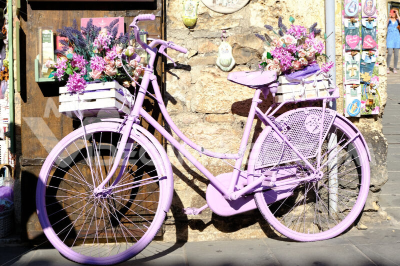 Bicycle painted purple with flowers in a souvenir shop in Assisi. - MyVideoimage.com