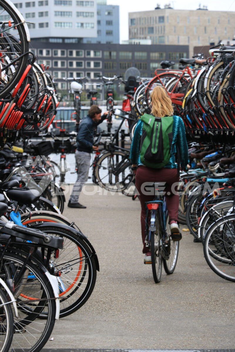 Bicycle parking at Amsterdam Central Station. A woman on a bike - MyVideoimage.com