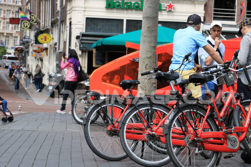 Bicycle parking at Amsterdam. Some guys on red public bikes. - MyVideoimage.com