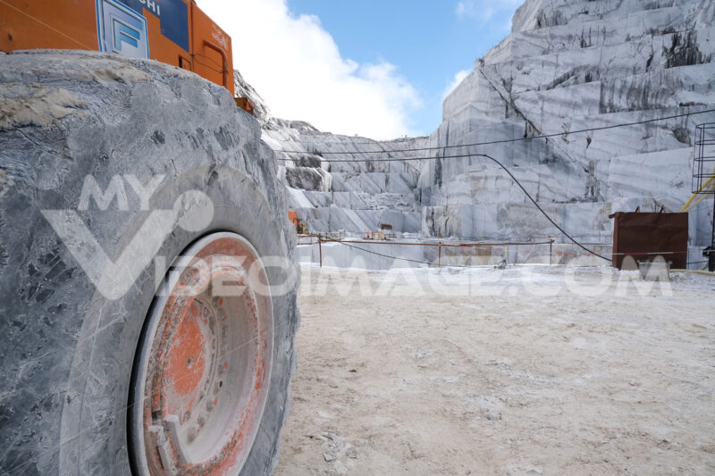 Big wheel of excavator. Wheel loader in a white marble quarry near Carrara. Stock photos. - MyVideoimage.com | Foto stock & Video footage