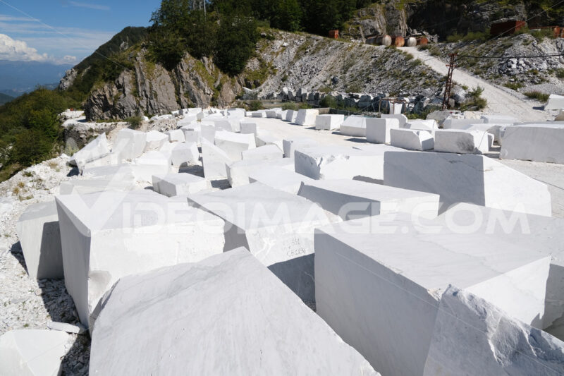 Blocchi di marmo di Carrara. Blocks of white Carrara marble deposited in a square near the quarries. Foto stock royalty free. - MyVideoimage.com | Foto stock & Video footage