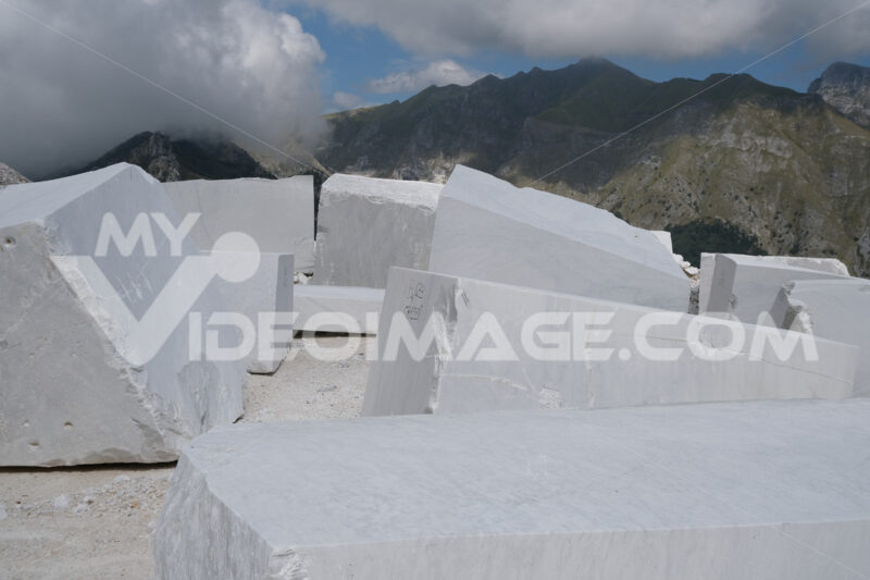 Blocchi di marmo grezzo. Blocks of white Carrara marble deposited in a square near the quarries. Foto stock royalty free. - MyVideoimage.com | Foto stock & Video footage