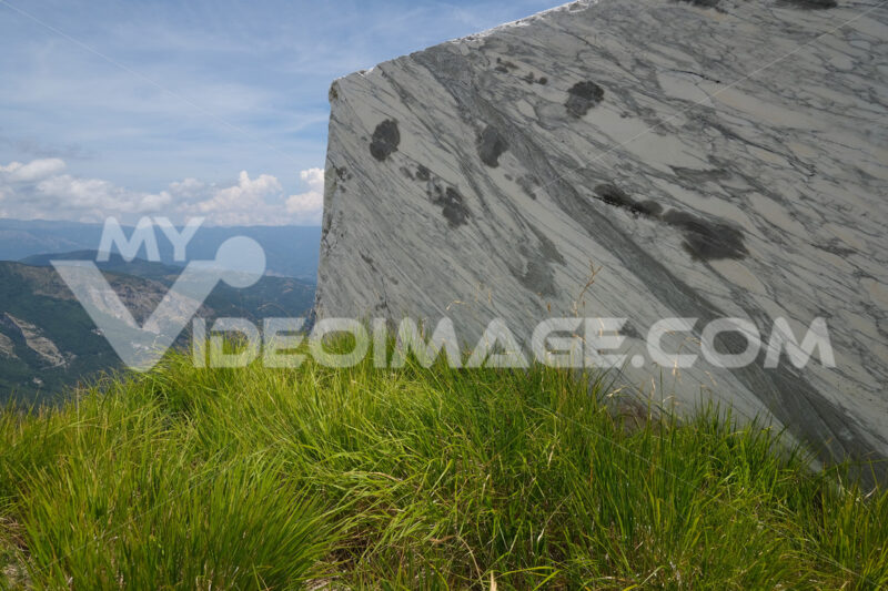Blocco di marmo Block of white veined marble resting on a green lawn in the Apuan Alps. Foto stock royalty free. - MyVideoimage.com | Foto stock & Video footage